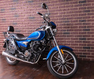 Blauwe die motor voor een bakstenen muur wordt geparkeerd stock foto's