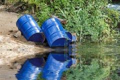 Blauwe die olietrommels in het water worden geworpen royalty-vrije stock afbeeldingen
