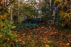 Blauwe die omheining door bomen en struiken wordt omringd stock foto's