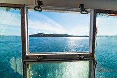 Blauwe die overzees in Sardinige door een veerbootvenster wordt gezien stock foto's