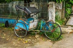 Blauwe die pedicap of driewieler in kant van de weg dichtbij struik en muur met niemand rond foto wordt geparkeerd in Depok Indon Stock Afbeeldingen