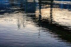 Blauwe die riviertextuur met brug daarin wordt weerspiegeld Stock Foto's