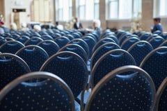 Blauwe die stoelen op een rij in de zaal worden opgesteld Royalty-vrije Stock Foto's