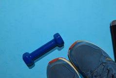 Blauwe domoor, tennisschoenen en smartphone die training op plan op blauwe achtergrond wijzen royalty-vrije stock foto's