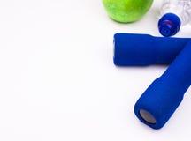 Blauwe domoren met een fles water en een groene appel op een witte gymnastiekvloer, copyspace voor tekst Stock Foto