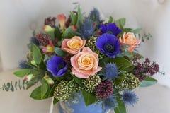 Blauwe doos met bloemen voor de vakantie Blauwe anemonen, rozen, eringium Stock Afbeeldingen