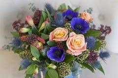 Blauwe doos met bloemen voor de vakantie Blauwe anemonen, rozen, eringium Stock Foto