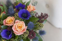 Blauwe doos met bloemen voor de vakantie Blauwe anemonen, rozen, eringium Royalty-vrije Stock Foto