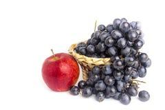 Blauwe druiven in mand en rode die appel op witte achtergrond wordt geïsoleerd Stock Foto