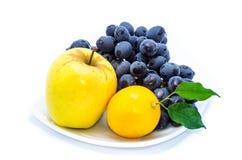 Blauwe druiven met gele appel en citroen op een witte plaat stock fotografie