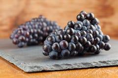 Blauwe druivenclusters op leiraad Royalty-vrije Stock Foto's