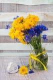Blauwe en gele kleuren van boeket de wilde bloemen in een vaas Stock Afbeeldingen