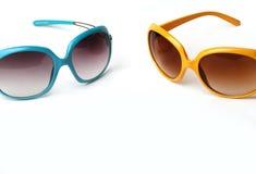 Blauwe en gele zonnebril op een witte achtergrond stock afbeeldingen