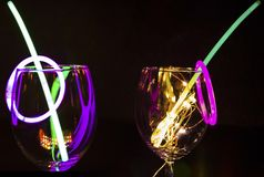 Blauwe en groene gloedstok op een wijnglas met nieuwe jaarviering met kleurrijke lichte relection aginst de donkere partij als ac stock foto