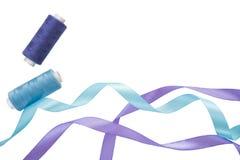 Blauwe en purpere krullende satijnlinten, spoelen van blauwe en purpere draad op een wit Horizontale banner met twee satijnlinten stock foto's