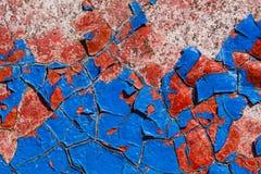Blauwe en rode oude verf op een muur stock foto