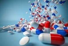 Blauwe en rode pillen die op blauwe achtergrond vallen Stock Afbeelding