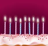 Blauwe en roze kaarsen op een verjaardagscake Stock Afbeeldingen
