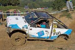 Blauwe en witte auto in de modder Stock Foto's