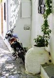 Blauwe en Witte die Bromfiets in Smalle Witte Gipspleisterstraten wordt geparkeerd in Griekenland royalty-vrije stock afbeeldingen