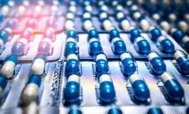Blauwe en witte die capsulespil in blaarpak met mooi patroon wordt geschikt globaal gezondheidszorgconcept Antibioticadrug stock foto