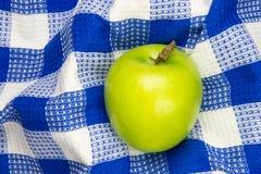 Blauwe en witte geruite lijstdoek met groene appel royalty-vrije stock afbeelding