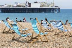Blauwe en witte gestreepte deckchairs op het strand van Brighton Stock Foto's