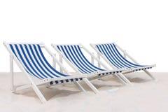 Blauwe en witte gestreepte ligstoel drie op isola van het zandstrand stock afbeelding