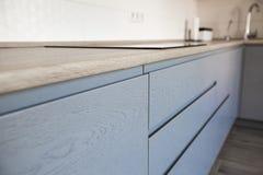 Blauwe en witte kabinetten in modern keukenbinnenland stock afbeelding