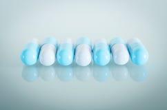 Blauwe en witte medische capsules Stock Fotografie