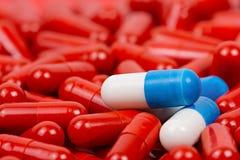 Blauwe en witte pillen op achtergrond van rode pillen Stock Foto's