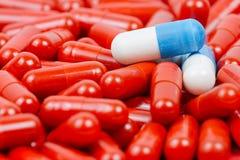 Blauwe en witte pillen op achtergrond van rode pillen Royalty-vrije Stock Fotografie