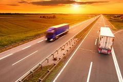 Blauwe en witte vrachtwagen in motieonduidelijk beeld op de weg Royalty-vrije Stock Fotografie