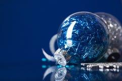 Blauwe en zilveren Kerstmisornamenten op donkerblauwe achtergrond Stock Foto