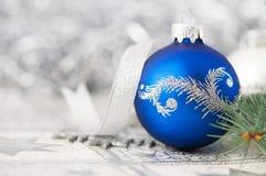 Blauwe en zilveren Kerstmisornamenten op heldere achtergrond Stock Afbeelding