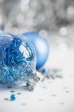 Blauwe en zilveren Kerstmisornamenten op heldere vakantie B Stock Afbeeldingen