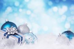 Blauwe en zilveren Kerstmisscène met snuisterijen en gift Stock Foto's