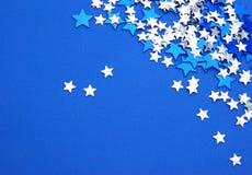 Blauwe en zilveren sterren op blauwe achtergrond Stock Fotografie