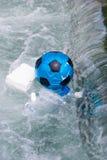 Blauwe en zwarte bal en plastiekenflessen en dozen die in t drijven stock foto