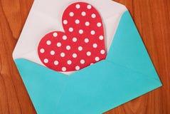 Blauwe envelop en rood hart met witte stippen op een houten lijst stock afbeelding