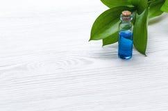 Blauwe essentie helende tint op witte houten lijstachtergrond Essentiële olie stock fotografie