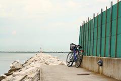 Blauwe fiets die door rotsweg wordt geparkeerd die in het overzees leidt Stock Afbeelding
