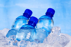Blauwe flessen water in ijs Stock Foto