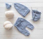 Blauwe gebreide babykleren met witte breiende garens stock fotografie