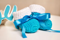 Blauwe gebreide babyschoenen met blauw lint Stock Fotografie