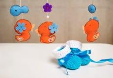 Blauwe gebreide babyschoenen met een blauw lint rond speelgoedrammelaars. Stock Fotografie