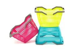 Blauwe, gele en roze plastic het winkelen mand. Stock Foto's