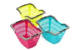 Blauwe, gele en roze plastic het winkelen mand. Stock Foto