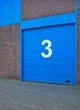 Blauwe geschilderde garagedeur in een oud gebouw stock foto