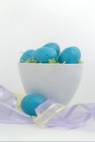 Blauwe gespikkelde eieren in Pasen-gras met pastelkleurlint Stock Afbeeldingen